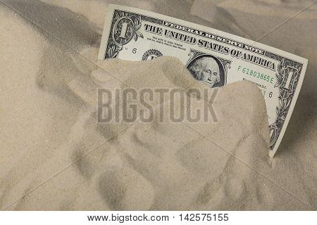 Finance concept. One dollar bank note in the sand.