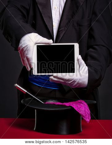 Magician holding tablet pc over his accessories for work, advertising and illusion