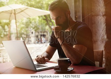 Concentrated Young Bearded Businessman Wearing Black Tshirt Working Laptop Urban Cafe.Man Sitting Table Cup Coffee Listening Music.Coworking Process Business Startup.Blurred Background.Color Filter