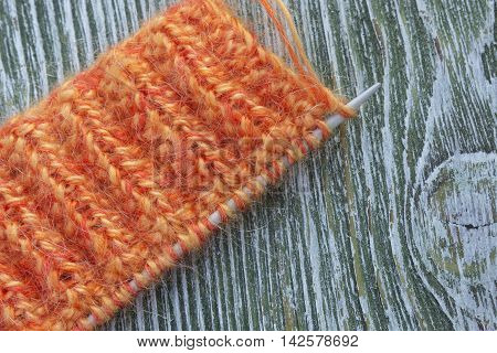 Knitting orange mohair wool and needles on wooden green rustic background. The beginning on knit cloth