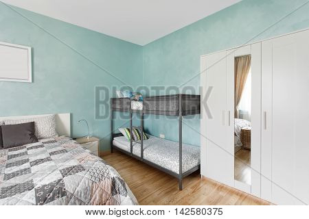 Bedroom in blue color with a double and a two-tier beds. Interior design