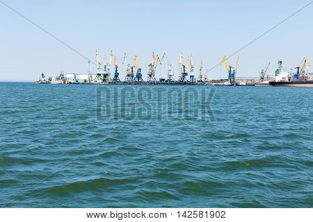 Cargo port with lots of cranes and ships, view from the sea