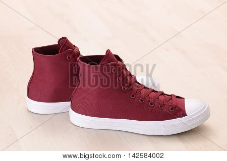 Red canvas sneakers on wooden plank floor