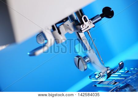 Modern sewing machine foot on blue background with copy space.