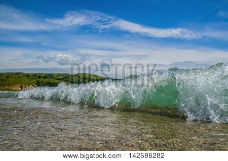 Emerald oncoming sea wave on the beach