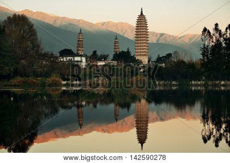 Ancient pagoda in Dali old town with lake reflection at sunrise, Yunnan, China.