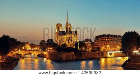 Notre Dame de Paris at dusk panorama over River Seine as the famous city landmark.