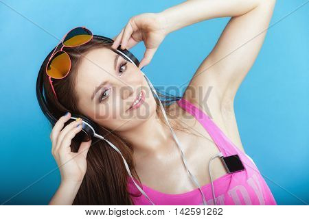 Fashion teen girl headphones listen music mp3 player Fresh energetic young woman relax happy and dancing blue background
