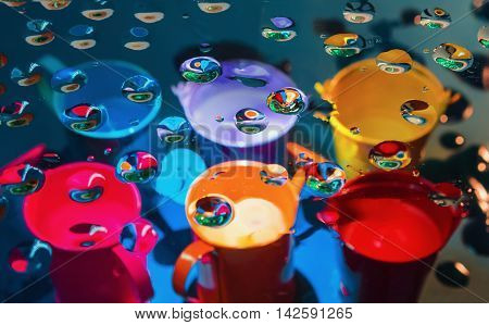 Multicolored abstract background - view through glass with drops of liquid on a blurry colorful watering cans and buckets. Selective focus on foreground.