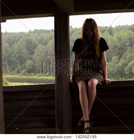 Young girl sitting on the railing of a wooden gazebo. The light falls on the legs, the face remains in the shadows.