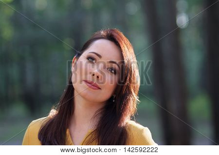 Portrait of a beautiful woman on a forest background. People