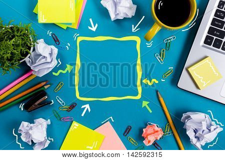 Office table with notepad, computer and coffee cup on blue background. Business creative consept top view