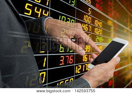 Businessman's hand using smart phone with display board of Stock market quotes in background.