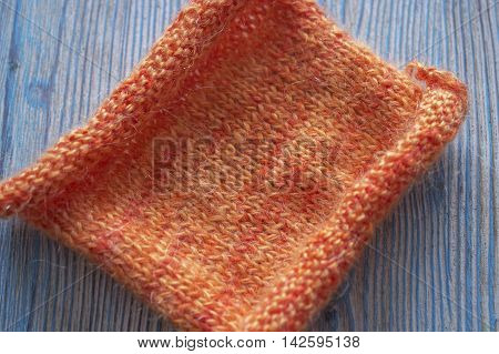 Knitting orange mohair wool on wooden green rustic background. The beginning on knit cloth