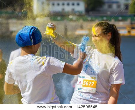 Ukraine, Kyiv - 08/14/2016.  Kyiv color run. Run 5 km from the colors of Holi. Funny girl throw each other in the face paint Holi.