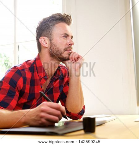 Man Thinking Sitting At Desk With Stylus