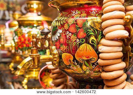Khokhloma painting traditional Russian samovar with bunch of crackers bagels