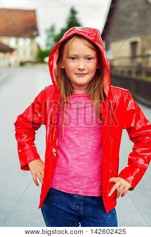 Vertical outdoor portrait of a cute little girl of 8-9 years old on a cloudy day, wearing bright red rain jacket