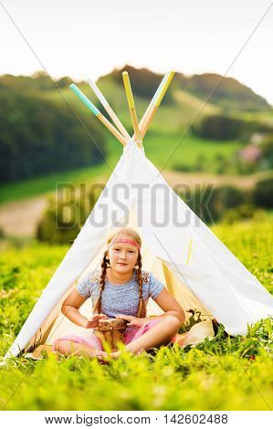 Outdoor portrait of a cute little girl playing music