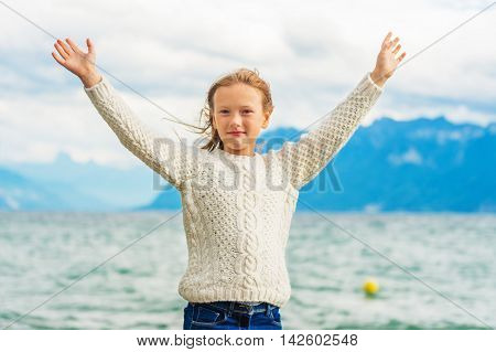 Cute little girl of 8 years old playing by the lake on a very windy day, wearing warm white knitted pullover, arms wide open