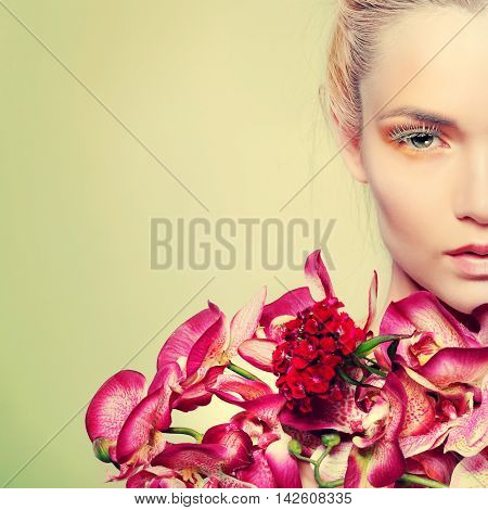 Beautiful girl, isolated on a light - green background with varicoloured flowers, emotions, cosmetics