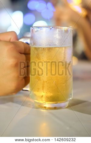 Glass of beer against barrels in hand