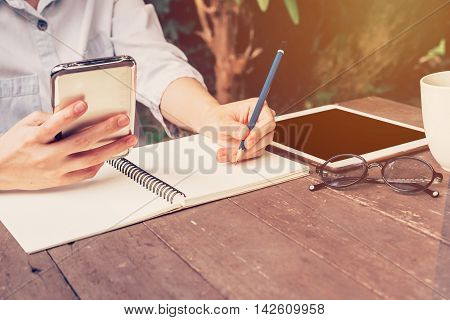 Asian Woman Hand Holding Phone And Pencil Writing Notebook In Coffee Shop With Vintage Toned