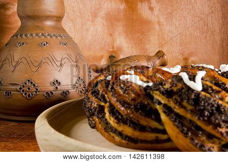 Clay pots for coffee and a roll with poppy seeds on a wooden background