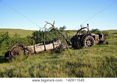 An old manure spreader and tractor are left out in a ranch land pasture