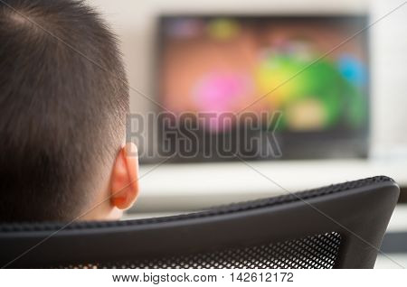 kid sitting and watching television broadcasting cartoon at home