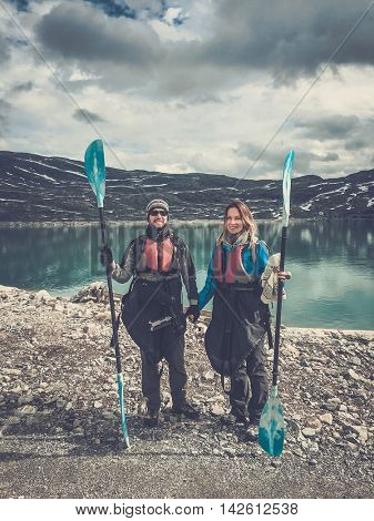 Happy couple of kayakers standing with paddles near Styggevatnet lake, Jostedalsbreen glacier. Norway