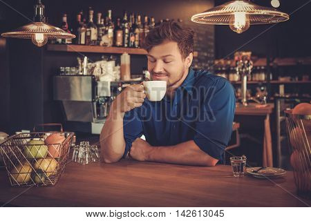 Handsome barista tasting a new type of coffee in his coffee shop.