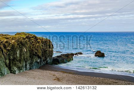 View of rocks at Black Beach and North Atlantic Ocean in the north of Iceland