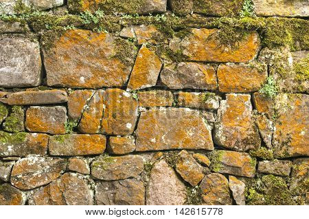 Stone wall with moss and lichen closeup as background