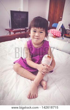 Full body. Child injured on bed in bedroom. Asian lovely girl looking at camera bloody wound on her knee with bandage. Human health care and medicine concept. Vintage tone effect.