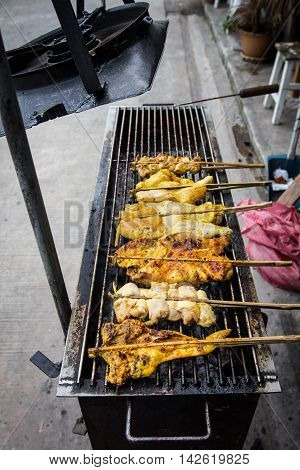 Grilling chicken plugged with bamboo on the tray