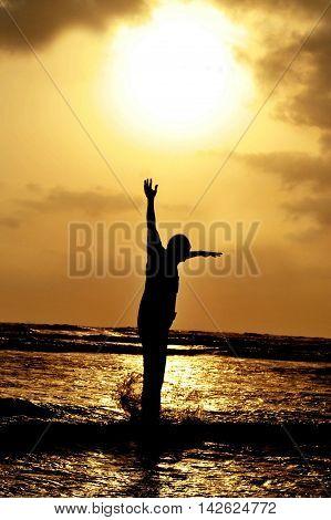 SIlhouette of a man jumping against setting sun on karacchi beach clifton Pakistan