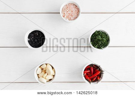Food seasoning variety on white wooden background, flat lay. Frame of bowls with black and pink sea salt, parsley, chili and garlic, free space. Natural organic food, cooking concept