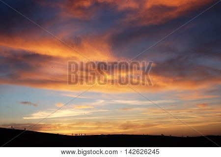 brilliant colorful sunset over sand dunes with silhouettes wispy clouds dramatic