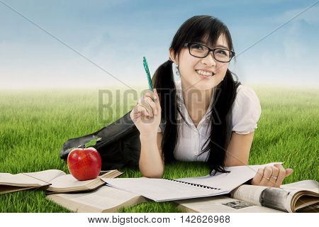 Photo of a clever female high school student studying with book while lying on the meadow