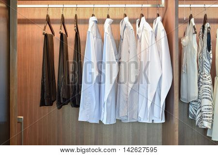 Row Of White Shirts Hanging In Wooden Wardrobe