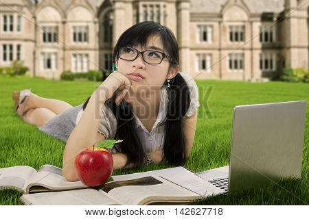 Portrait of a pretty schoolgirl daydreaming on the park while studying with book and laptop