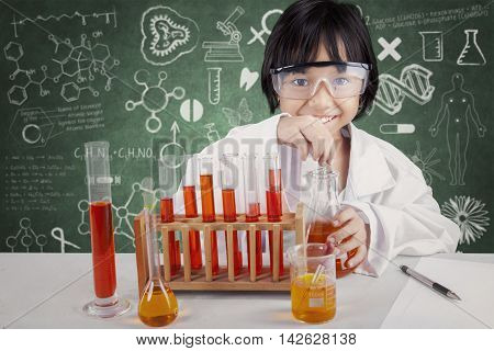 Portrait of little schoolgirl wearing coat and make chemistry research in the laboratory