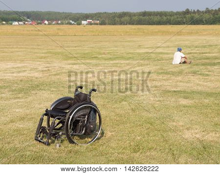 The Moscow region - 15 July 2016: Black wheelchair standing in a field with green grass mowed at festevale