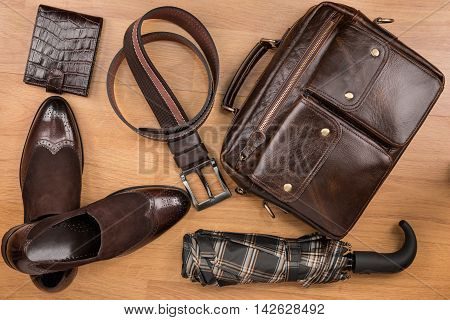 Classic brown shoes briefcase belt and umbrella on the wooden floor can be used as background