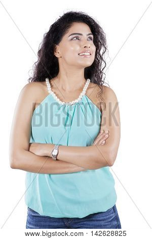Portrait of a young Indian woman standing in the studio while daydreaming isolated on white background