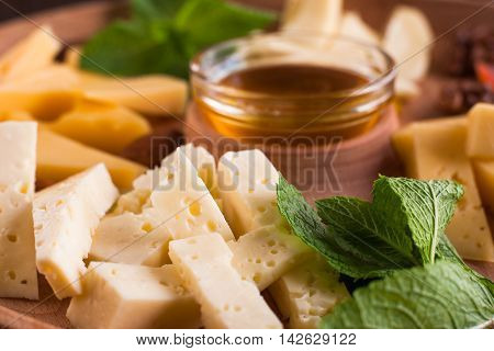 Cheese pieces with honey closeup. Tasty gourmet snack for wine, luxury lifestyle, regale food