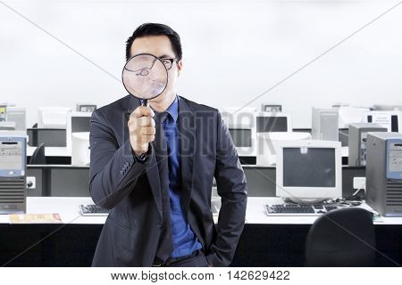 Photo of a male entrepreneur looking at the camera through a magnifying glass in the office