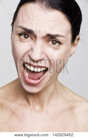 Portrait human emotion facial expression reaction attitude, frustrated angry woman   screaming  isolated on grey wall background.