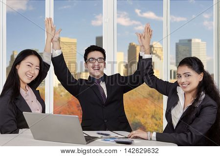 Portrait of three cheerful multiracial businesspeople celebrating their success and clapping hands together in the office